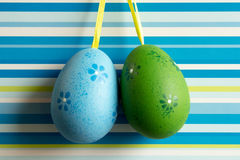 Blue and green hanged Easter eggs on striped background Royalty Free Stock Image