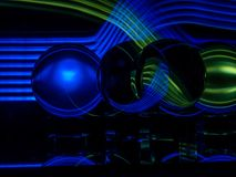 Blue and Green Light Waves Cross in the Background and Reflect in the Lenballs royalty free stock photography