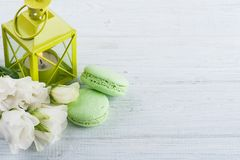 Blue green macaroons and lit candle in lantern Royalty Free Stock Images