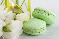 Blue green macaroons and lit candle in lantern Royalty Free Stock Photos