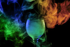 Blue-green-orange smoke in the glass. Halloween. Stock Photos
