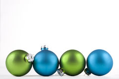 Blue and green ornaments. Blue and green Christmas ornaments lined up, isolated Royalty Free Stock Photography