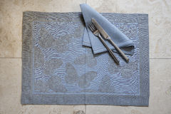 Blue Green Rectangular Placemat with Butterfly Design. A stone blue placemat with embroidered butterfly design laid spread out with matching color napkin knife Stock Photo