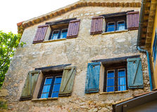 Blue Green and Red Shutters on Old Stone Building Stock Photography