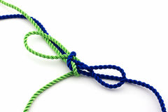 Blue and green ropes tied in a bow, isolated Royalty Free Stock Image