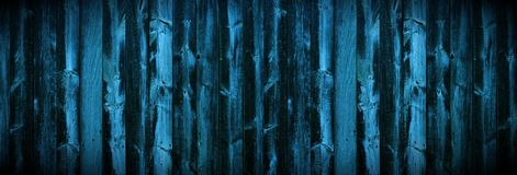 Blue green rustic wooden fence. Dark wall is made of narrow vertical strips of wood texture. Stock Photos