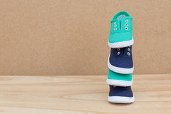 Blue and green shoes on a wooden table Stock Images