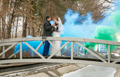 Blue and green smoke covering newlywed couple dancing on bridge Royalty Free Stock Photos