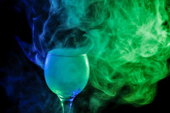 Blue and green smoke in a glass. Halloween. Abstract art. Hookah blue - green smoke in a cocktail glass on a white background. Witch potion background for Stock Image