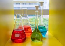 Blue and green solution in the glass beakers on yellow shelf. Red, green and blue solution in the glass beakers on yellow shelf at science laboratory Stock Photos