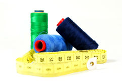 Blue and green threads with tape measure. On white background Stock Image