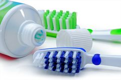 Blue, green toothbrushes and toothpaste are isolated on a white royalty free stock images