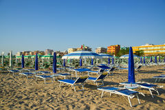Blue and green umbrellas and chaise lounges on the beach of Rimini in Italy.  stock image