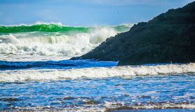 Waves crashing ashore, Bethels Beach, Auckland, New Zealand. Blue and green water and with capped waves breaking ashore against rocks royalty free stock photo