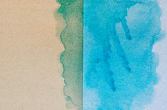 Blue and green watercolor on brown paper background.  stock image