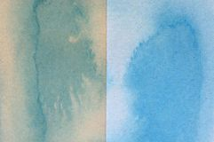 Blue and green watercolor on brown paper background.  stock photography
