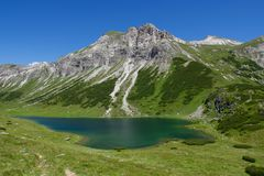 Emerald alpine lake with mountains Royalty Free Stock Image