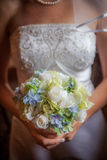 Blue, green, white bouquet held by bride. Stock Photos