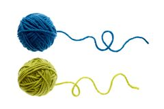 Blue and green woolen balls over white background. Two balls of wool partially unrolled stock photography