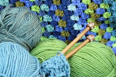 Blue and Green Yarn Crafts. Wooden knitting needles with blue and green yarn with crochet afghan blanket in background stock photography