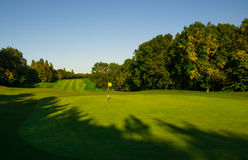 Blue Green and Yellow - Golf Paradise. Golf fairway with yellow flag in green British countryside Royalty Free Stock Photo