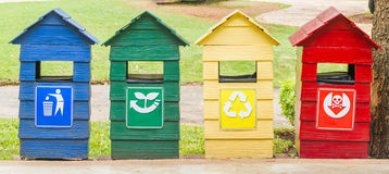 Blue, green, yellow and red bins on stand near footpath. Stock Photography