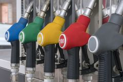 Blue, green, yellow, red and gray fuel pistols on fuel station close-up. Fuel pistols close up at the gas station close-up Stock Photos