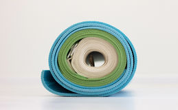 Blue and green yoga mats and white strap twisted together Stock Images
