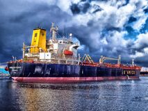 Blue and Grey Cargo Ship Navigating Stock Photography