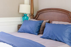 Blue and grey pillows on classic wooden bed with modern lamp Royalty Free Stock Images