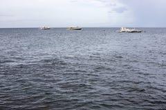 Blue grey sea and sky view photo. Rainy day on seaside. White boats in open sea. Rainy season on tropical island stock photography