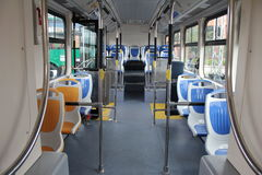 Blue and grey seats for passengers in saloon of empty city bus. The main entrance of modern bus. Interior of a modern empty city bus, Blue and grey seats for Stock Photo
