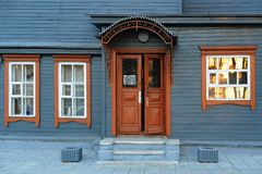 Blue grey wooden house facade with brown open door Stock Photos