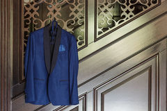 A blue groom`s jacket hanged on an wooden staircase. Indoor shot with natural light Stock Images