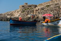 Blue Grotto boat trip, Malta. BLUE GROTTO, MALTA - AUGUST 23, 2017: Tourists taking a boat trip at the Blue Grotto. The sea caves of Blue Grotto and natural arch Stock Photography