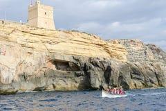 The coast at Blue Grotto in the Malta island. Blue Grotto, Malta - 3 November 2017: tourists visiting the coast by boat at Blue Grotto in the Malta island Royalty Free Stock Photo