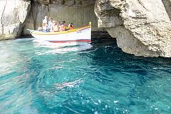 Coast at Blue Grotto in the Malta island. Blue Grotto, Malta - 3 November 2017: tourists visiting the coast by boat at Blue Grotto in the Malta island Stock Photography