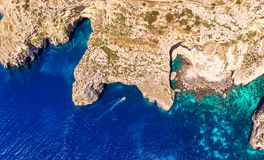 Blue Grotto in Malta. Pleasure boat with tourists runs. Natural arch window in the rock. Aerial top view. royalty free stock images