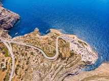 Blue Grotto in Malta. Pleasure boat with tourists runs. Natural arch window in rock. Aerial top view. royalty free stock photography