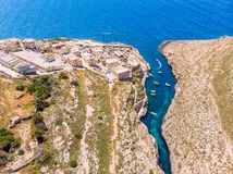 Blue Grotto in Malta. Pleasure boat with tourists runs. Natural arch window in rock. Aerial top view. royalty free stock photo
