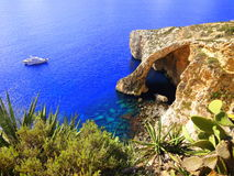 Blue Grotto, Malta. Blue Grotto, sea cave and natural rock on the island of the south coast of Malta in Europe. A small ship on the blue ocean in the background stock photos