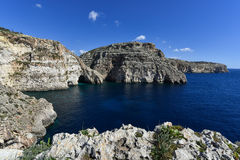 Blue grotto seacoast Malta. Limestone rocks with caves and clear water near popular tourist attraction Blue Grotto on a sunny day Stock Photos