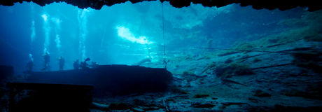 Blue Grotto Underwater Panoramic. A view of Blue Grotto looking out from the deeper water cavern ledge looking back to the entry platform where Instructor and Royalty Free Stock Image