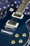 Blue Guitar on Flag Background. A blue wood electric guitar shot on an American flag background in the vertical format Royalty Free Stock Image