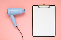 Blue hair dryer and clipboard on pink background Stock Image