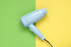 Blue hair dryer on green and yellow background Stock Photo