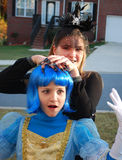 Blue-haired Cinderella and Witch. Scared blue-haired girl in Cinderella costume with white gloves and smiled witch stock photography