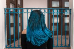 Blue Haired Woman Facing Metal Fence stock images