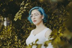 Blue-haired Woman Surrounded by Green-leafed Plants stock photos