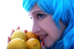 Blue hairs girl vs lemons Royalty Free Stock Photos